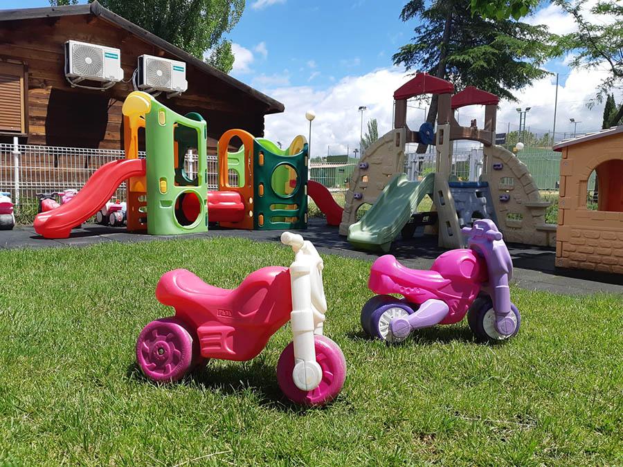 Juguetes, motos y triciclps en los jardines de la escuela infantil en las rozas pequeños astronautas